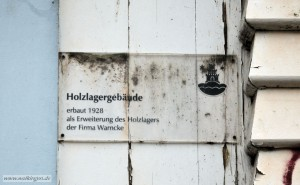 Tafel an der Fassade des Holzlagergebäudes